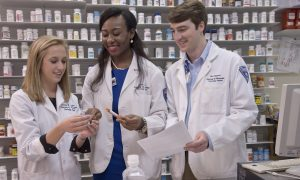 Three pharmacy students standing in front of a wall of pill bottles